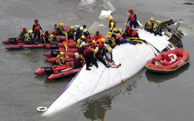 epa04602993 Search and rescue team members operate on a TransAsia Airways passenger plane crashed into the Keelung River in Taipei, Taiwan, 04 February 2015, shortly after taking-off from the Taipei Songshan Airport for Kinmen Island. Of the 58 people on board the ATR 72 plane, at least 12 were killed, 16 injured and the rest rapped inside the plane. There were 31 Chinese tourists on board the plane.  EPA/DAVID CHANG